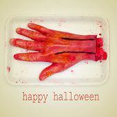 stock photo of amputation  - picture of a scary amputated hand and the sentence happy halloween on a beige background - JPG