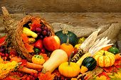 stock photo of wooden basket  - Harvest or Thanksgiving cornucopia filled with vegetables against wood - JPG