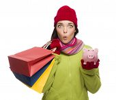Concerned Expressive Mixed Race Woman Wearing Winter Clothes Holding Shopping Bags and Piggy Bank Is