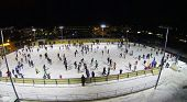 People skate on big ice rink at dark winter night. Aerial view