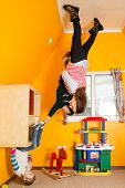 Family of three in children room upside down at inverted house