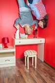 Two girls upside down in the bedroom above the dressing table