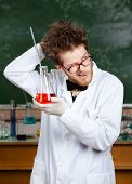 stock photo of mad scientist  - Mad professor scratches his head  handing flask - JPG