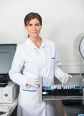 Portrait of female researcher with samples for coagulation analysis in lab poster