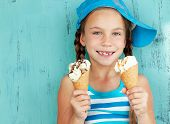 stock photo of 7-year-old  - Portrait of 7 years old kid girl eating tasty ice cream on blue background - JPG