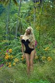 Beautiful young lady in black swimsuit with mighty tree