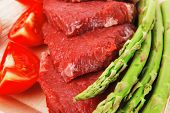 picture of flank steak  - fresh raw beef meat steak fillet on wooden plate with asparagus and tomatoes ready to prepare - JPG