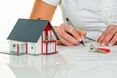 foto of home addition  - a woman signs a contract to purchase a home with a real estate agent - JPG
