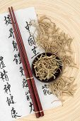 pic of honeysuckle  - Chinese herbal medicine of dried honeysuckle flowers with mandarin calligraphy script on rice paper describing the medicinal functions to maintain body and spirit health and balance body energy - JPG