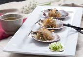 stock photo of scallop-shell  - A Korean delicacy called Chop Chae noodles served on scallop shells with a side of diced cucumber - JPG