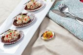 picture of scallop-shell  - A close up of tuna salad mixed with diced red bell pepper and topped with chives served on scallop shells with a side of freshly diced relish - JPG