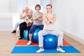 stock photo of senior class  - Full length portrait of trainer and senior customers sitting on fitness balls in exercise class - JPG