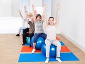 foto of senior class  - Full length portrait of trainer and senior customers stretching on fitness balls in exercise class - JPG