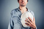pic of blue-collar-worker  - A proud blue collar worker is holding a hard hat - JPG