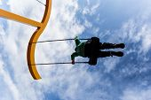 foto of swing  - Silhouette of a boy swinging on a swing against a deep blue sky with puffy clouds - JPG