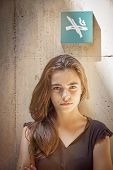 stock photo of teen smoking  - strictly looking teenager girl with no smoking sign on the wall behind her - JPG