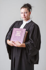 foto of toga  - thirty caucasian woman wearing canadian lawyer toga and a red criminal law book - JPG