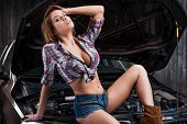 stock photo of cleavage  - Attractive young woman with beautiful cleavage holding hand in hair while leaning at the car in auto repair shop - JPG