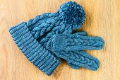 stock photo of knitted cap  - knitting cap and mittens on wooden background - JPG