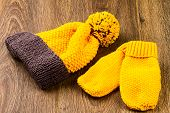 pic of knitted cap  - yellow knitting cap and mittens on wooden background - JPG
