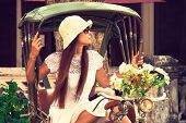 image of rickshaw  - Young white woman sitting in rickshaw with bunch of flowers and looking away - JPG