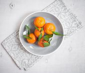 stock photo of clementine-orange  - Clementine tangerines with green leaves on white wooden background in a gray bowl - JPG
