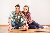 picture of laminate  - Young couple are installing laminate flooring in the room - JPG