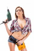 pic of protective eyewear  - Beautiful young woman with tool belt and protective eyewear holding drill while standing against white background - JPG