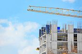 pic of framing a building  - Crane and building construction site against blue sky - JPG