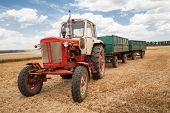 image of tractor  - old tractor in field against a cloudy sky - JPG