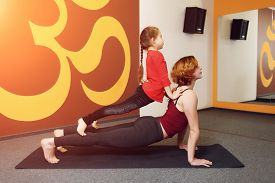 stock photo of om  - Mother and child yoga practice on the background of the Indian symbol of OM - JPG
