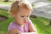 pic of pouting  - Outdoor closeup portrait funny Caucasian blond baby girl resentfully pouts - JPG