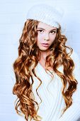 stock photo of beret  - Cute teenager girl with beautiful long curly hair wears white knitted jersey and beret - JPG