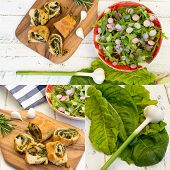 foto of rocket salad  - Dough rolls strudel with swiss chard and chorizo on chopping board young garlic with lettuce and rocket leaves salad chopped radishes white painted wood background - JPG