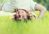 stock photo of upside  - Portraits of happy kids playing upside down outdoors in summer park walking on hands - JPG