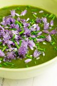 image of edible  - Swiss chard and potato cream soup with chopped chives with edible chives flowers in green ceramic bowl - JPG