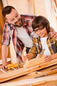 stock photo of carpenter  - Happy young male carpenter embracing his son while working with wood in his workshop - JPG