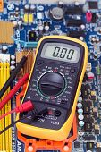 picture of  multimeter  - Digital multimeter and circuit board with radio components for the computer - JPG