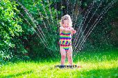 stock photo of fountain grass  - Child playing with garden sprinkler - JPG