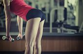 stock photo of bums  - Young beautiful athletic girl performs the slopes with a dumbbell in the gym - JPG