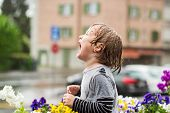 picture of rain  - Cute little boy playing under the rain outdoors, catching rain drops by his mouth