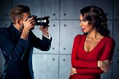 picture of young woman posing the camera  - Young woman in red dress posing to man photographer - JPG