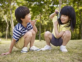 picture of playmate  - little asian girl looking at little asian boy through a magnifier outdoors in a park - JPG