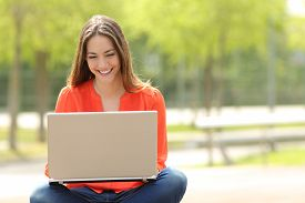 stock photo of in front  - Front view of a happy student girl working with a laptop in a green park of an university campus - JPG