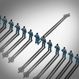 picture of opposites  - Different business thinking and independent thinker concept and new leadership concept or individuality as a group of people cast shadows with the shadow of one businessman going in the opposite direction as a business icon for innovative thinking - JPG