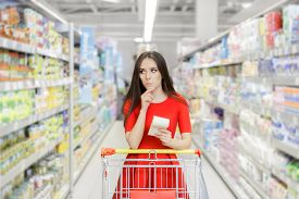 foto of department store  - Young girl in a market store with a shopping list thinking what to buy - JPG