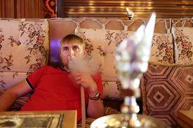 stock photo of shisha  - Man smoking shisha in the arabic cafe - JPG