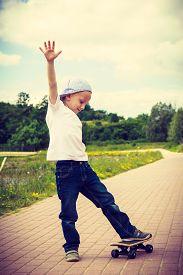 stock photo of skateboard  - Sporty child balancing on skateboard outdoor - JPG