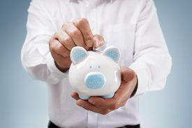 picture of insert  - Businessman inserting a coin into a piggy bank concept for business savings - JPG