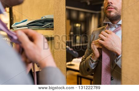sale, shopping, fashion, style and people concept - close up of young man in suit choosing and tying